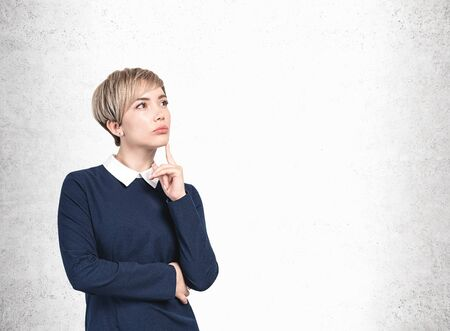 Portrait of thoughtful young blonde businesswoman in dark blue dress. She is thinking with finger on chin standing near concrete wall. Concept of decision making. Mock up