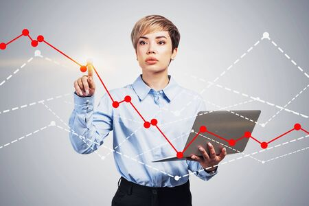 Young businesswoman with short blonde hair holding laptop and working with graphs over gray background. Concept of hi tech and computer science.