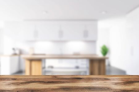 Blurred interior of modern kitchen with white walls, concrete floor, white countertops and cupboards and wooden island for cooking. Table for your product in foreground. 3d rendering Banco de Imagens