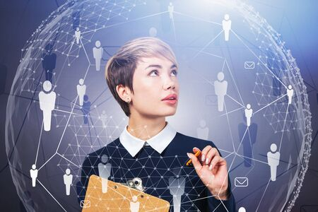 Young businesswoman with clipboard standing over grey background with double exposure of social network interface and planet hologram. Concept of communication. Toned image Stock Photo