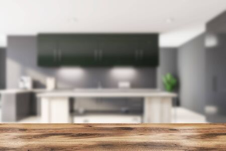 Blurred interior of modern kitchen with gray walls, wooden floor, gray countertops, green cupboards and wooden island for cooking. Table for your product in foreground. 3d rendering