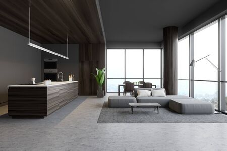 Interior of stylish kitchen and living room with gray and wooden walls, concrete floor, island with sink and cooker, dining table and comfortable grey sofa. 3d rendering Banco de Imagens