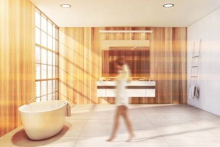 Woman walking in modern bathroom with wooden and white walls, tiled floor, double sink and comfortable bathtub. Toned image blurred Imagens