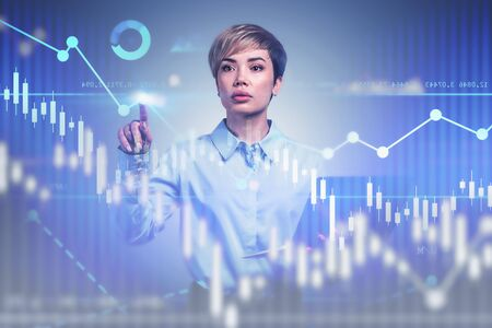 Smart young business consultant with laptop working with forex charts and business interface. Concept of hi tech and women in business. Toned image double exposure
