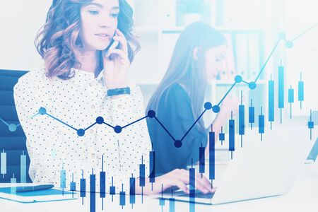 Two young businesswomen working in modern office with gadgets with double exposure of forex graphs. Concept of business analysis and stock market. Toned image
