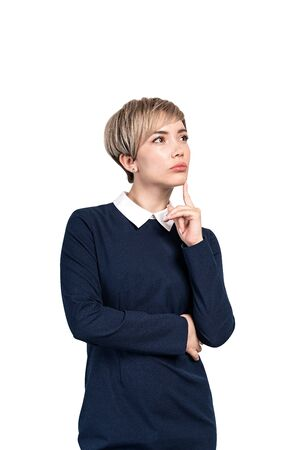 Isolated portrait of thoughtful young blonde businesswoman in dark blue dress. She is thinking with finger on chin. Concept of decision making