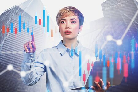 Beautiful young business consultant with laptop working with digital graphs in city. Concept of stock market. Toned image double exposure