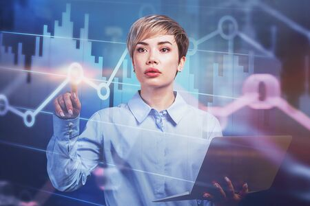 Young businesswoman with laptop working with virtual diagrams. Concept of stock market and hi tech. Toned image double exposure Stock Photo
