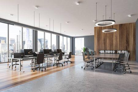 Ecke des modernen Büros mit grauen und hölzernen Wänden, offener Raum mit grauen Computertischen und Konferenzraum mit Metallstühlen. 3D-Rendering Standard-Bild