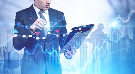 Un jeune homme d'affaires méconnaissable signe un contrat en ville avec une double exposition du graphique forex et des hommes d'affaires en arrière-plan. Concept de leadership et démarrage de haute technologie. Image tonique