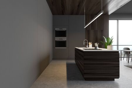 Interior of stylish kitchen with gray and wooden walls, concrete floor, dark wooden island with built in sink and cooker and two ovens. 3d rendering Banco de Imagens