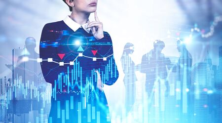 Thoughtful young business leader in black dress standing in modern city with her team silhouettes in background and double exposure of forex graphs. Concept of leadership and stock market. Toned image