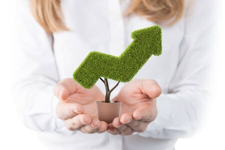 Unrecognizable blurry businesswoman hands holding potted plant shaped as growing arrow graph. Concept of investment and financial growth.