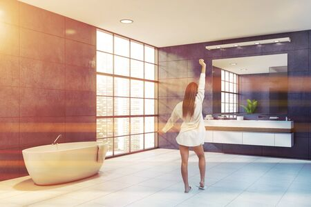 Woman in nightgown standing in modern bathroom with blue walls, tiled floor, double sink and comfortable bathtub. Toned image Imagens