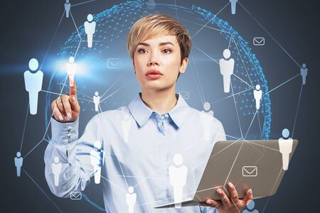 Young businesswoman with laptop working with social network icons and planet hologram over gray background. Concept of recruitment and international company. Toned image double exposure