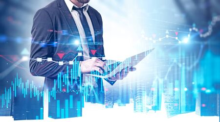 Bearded young businessman using laptop in modern city with double exposure of digital graph and network interface. Concept of stock market and smart city. Toned image