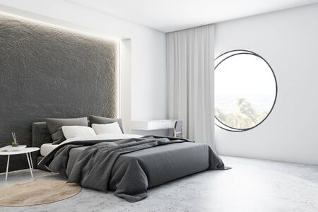 Corner of stylish bedroom with white and concrete walls, concrete floor, comfortable master bed with grey blanket and makeup table with mirror on it. Round window. 3d rendering