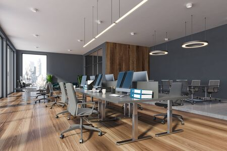 Corner of modern office with dark gray and wooden walls, open space area with grey tables and long conference table in background. 3d rendering