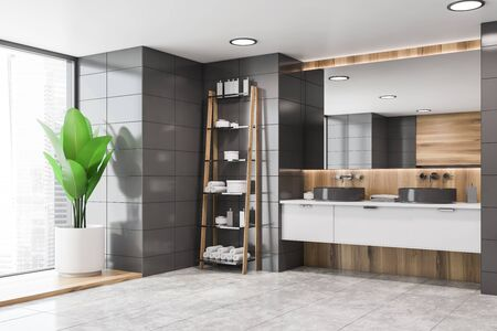 Corner of stylish bathroom with gray tile and wooden walls, double sink on white countertop with large mirror above it and rack with towels and creams. 3d rendering