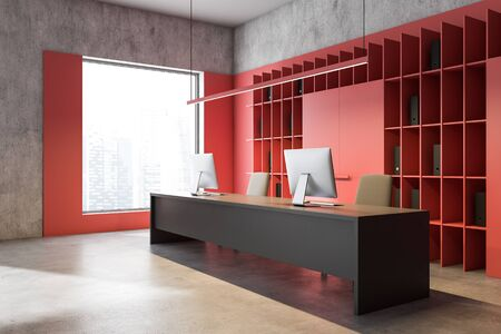 Corner of bright red loft office with concrete floor, red bookcase with folders and long gray table with two computers on it. 3d rendering