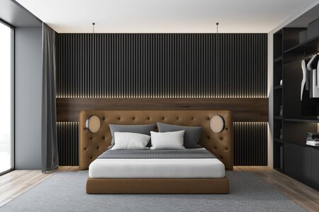 Interior of luxury bedroom with gray and wooden walls, wooden floor with carpet, leather king size bed and comfortable wardrobe. 3d rendering