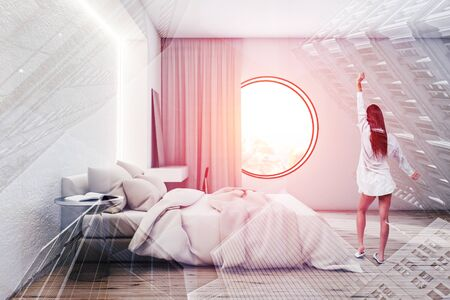 Rear view of young woman standing in luxury bedroom with white walls, king size bed, makeup table with mirror and round window. Toned image double exposure
