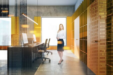 Smiling blonde businesswoman standing in modern loft office with yellow walls, bookcases and long computer table. Concept of management. Toned image double exposure 写真素材