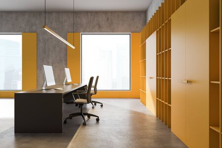 Side view of bright yellow loft office with concrete floor, yellow bookcase with folders and long gray table with two computers on it. 3d rendering