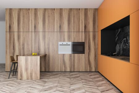 Interior of modern kitchen with wooden, orange and marble walls, orange countertops and cupboards, wooden bar with stools and two built in ovens. 3d rendering