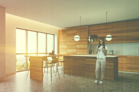 Young woman with smartphone standing in stylish kitchen corner with wooden countertops, bar with stools and island. Toned image double exposure 写真素材