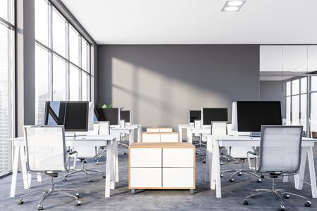 Interior of modern office or computer lab with gray walls, panoramic windows with cityscape, concrete floor and compact white tables with desktops on them. 3d rendering 写真素材