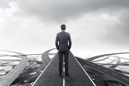 Rear view of young businessman standing on one of tangled roads over cloudy sky background. Concept of choosing the right way in business and life.