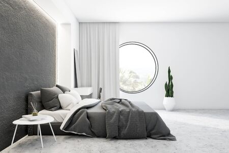 Side view of modern bedroom with white and concrete walls, concrete floor, comfortable master bed with grey blanket and makeup table with mirror on it. Round window. 3d rendering Stok Fotoğraf