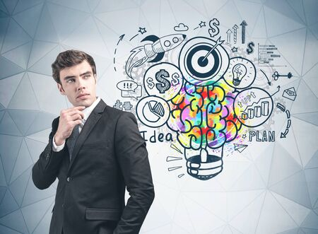 Thoughtful young businessman standing near gray wall with colorful business idea sketch drawn on it. Concept of planning and business strategy. Фото со стока