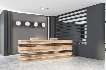 Corner of modern office with gray walls, tiled floor, wooden reception table with computers and clocks showing time in New York, Sydney, London and Tokyo. 3d rendering