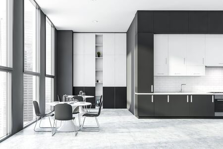 Interior of stylish kitchen with gray and white brick walls, concrete floor, dark gray countertops, white bookcase and two round dining tables. 3d rendering