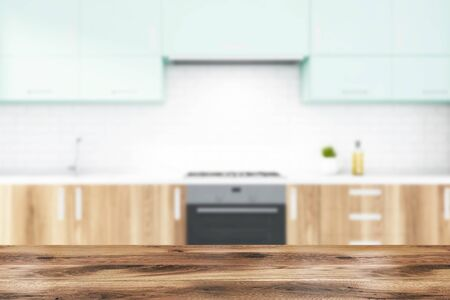 Close up of table for your product in blurry kitchen with wooden countertops with built in stove and sink and blue cupboards above them in modern white brick room. 3d rendering Фото со стока