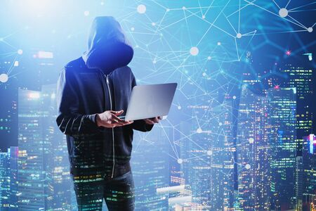 Unrecognizable young hacker with laptop standing in night city with double exposure of network interface. Concept of cybercrime. Toned image Stock Photo