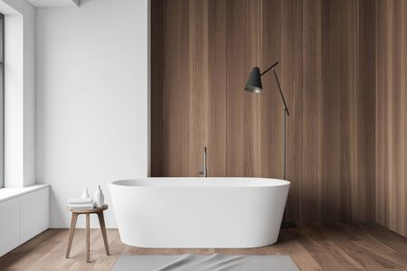 Interior of minimalistic bathroom with white and wooden walls, wooden floor, chair with towels, comfortable bathtub and floor lamp. 3d rendering
