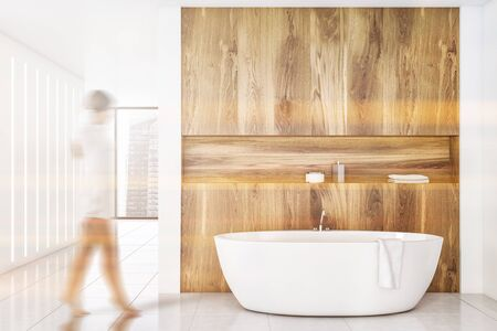 Blurry young woman walking in modern bathroom with wooden and white walls, tiled floor and comfortable white bathtub. Toned image Stok Fotoğraf