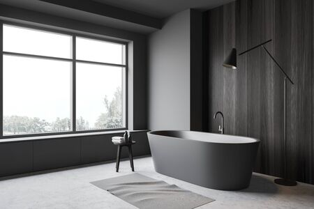 Corner of modern bathroom with gray and dark wooden walls, concrete floor, window with forest view, comfortable bathtub and floor lamp. 3d rendering