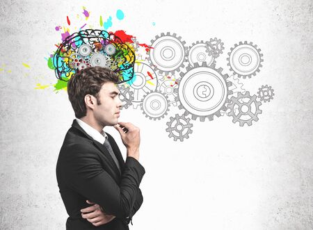 Side view of handsome young businessman standing near concrete wall with colorful brain sketch with gears. Concept of brainstorming and creative thinking
