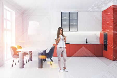 Young woman in casual clothes standing in luxury kitchen interior with white walls, orange countertops and massive marble dining table. Toned image double exposure