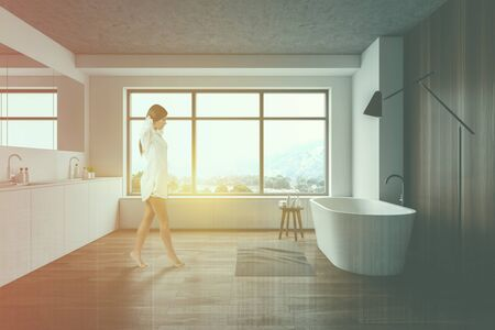 Young woman walking in modern bathroom with white and wooden walls, comfortable bathtub and double sink. Toned image double exposure