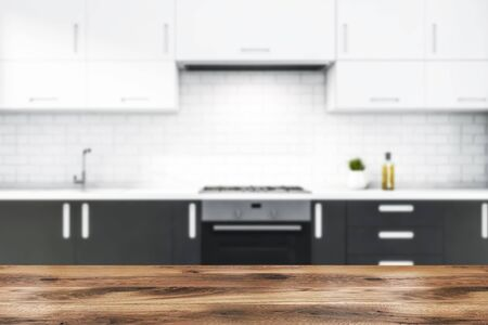 Close up of table for your product in blurry kitchen with gray countertops with built in stove and sink and white cupboards above them in modern white brick room. 3d rendering Фото со стока