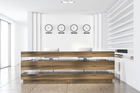 Interior of modern office with white walls, tiled floor, wooden reception table with computers and clocks showing time in New York, Sydney, London and Tokyo. 3d rendering