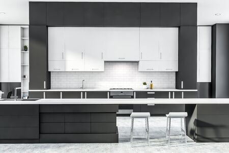 Interior of stylish kitchen with gray and white brick walls, concrete floor, dark gray countertops, and long bar with stools. 3d rendering