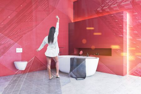Rear view of woman in nightgown standing in modern bathroom with red walls, comfortable white bathtub and toilet. Toned image double exposure Stok Fotoğraf