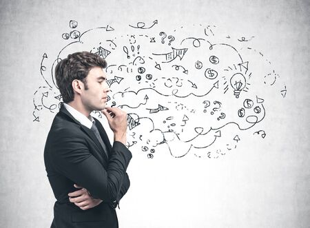 Side view of pensive young businessman in suit standing near concrete wall with business strategy sketch drawn on it. Concept of business idea and brainstorming