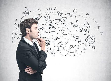 Widok z boku zamyślony młody biznesmen w garniturze stojący w pobliżu betonowej ściany z narysowanym na nim szkicem strategii biznesowej. Koncepcja pomysłu na biznes i burzy mózgów